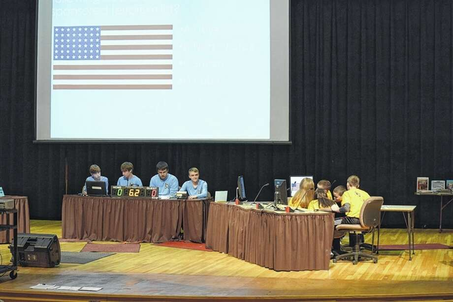 Members of the Eisenhower Elementary School gold team (right) discuss one of the first questions at the 23rd Regional Geography Bowl Wednesday night at the Jacksonville High School auditorium. Photo: Greg Olson | Journal-Courier