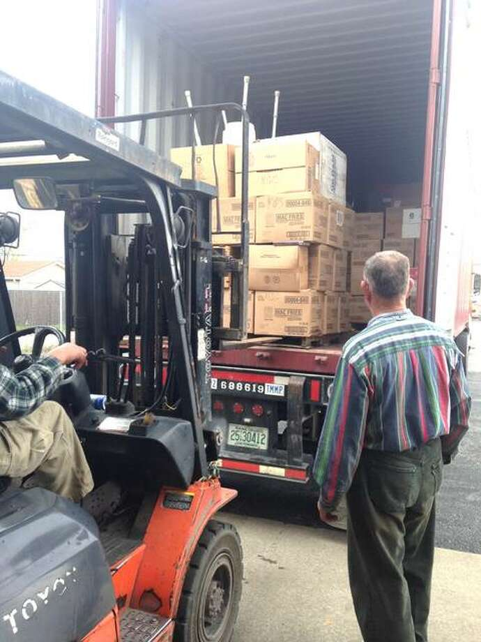 Clifford Clark, right, of Alton, watches as an employee of Clark Boat and Supply loads another pallet of donated books into a cargo box headed for National Public Library of Antigua and Barbuda. Photo: Linda N. Weller | The Telegraph