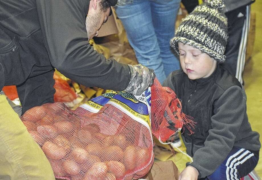 Seven-year-old Drew Gillespie, son of Amy and Brian Gillespie, helps Jared Reno sort food Thursday for the Central Illinois Mobile Foodbank at Knollwood Retirement Village in Jacksonville. About 200 people stood in line to receive food from the pantry. Photo: Samantha McDaniel-Ogletree | Journal-Courier