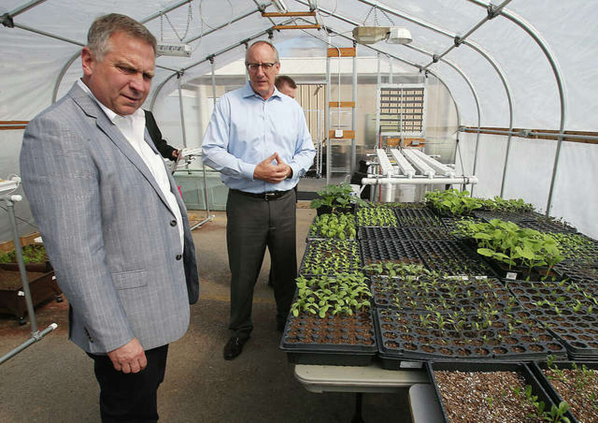Jonathan Becker, from Senior Services Plus in Alton, right, shows U.S. Rep. Mike Bost, left, one of the facility's greenhouses Wednesday during a tour of the center.