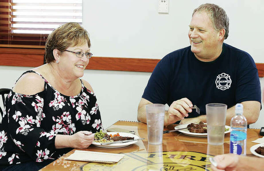 Alton Fire Department Capt. Walt Grabner shares a smile with his wife, Deborah, as she joined other firefighters in a steak luncheon for Grabner on his last day on the department after 25 years of service.