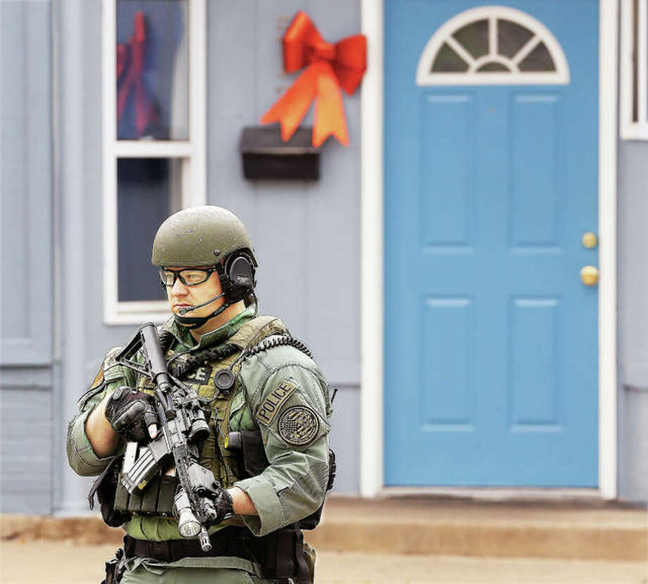 A member of the heavily armed Illinois Law Enforcement Alarm System tactical unit stands guard protecting the perimeter in the middle of Ridge Street in Alton Tuesday.