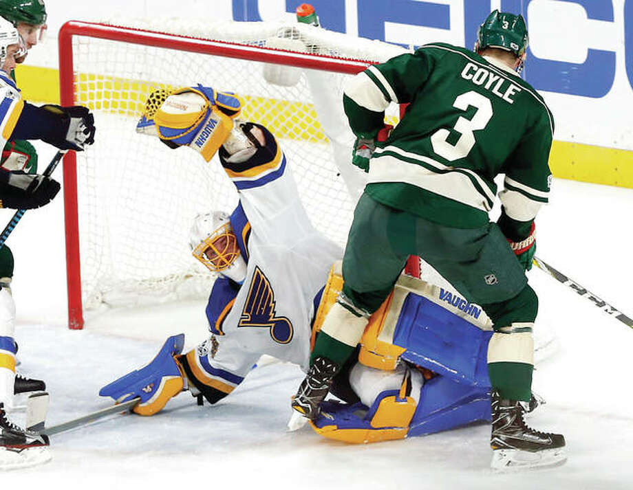 Blues goalie Jake Allen stops a shot by Minnesota Wild's Charlie Coyle, right, during Game 1 of their first-round Stanley Cup playoff series Wednesday in St. Paul, Minn. Allen stopped 51 of 52 shots and the Blues won 2-1 in overtime. Photo: AP