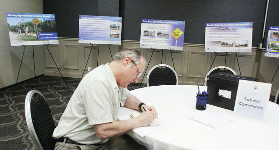 Andy Sisk, of Kirkwood, Mo., a representative of the GM&O Historical Society, fills out a comment card at a public meeting on Illinois' high-speed rail Wednesday at the Atrium Hotel & Conference Center. Construction on the project is expected to be finished by fall, with high-speed trains possibly running by the end of the year.