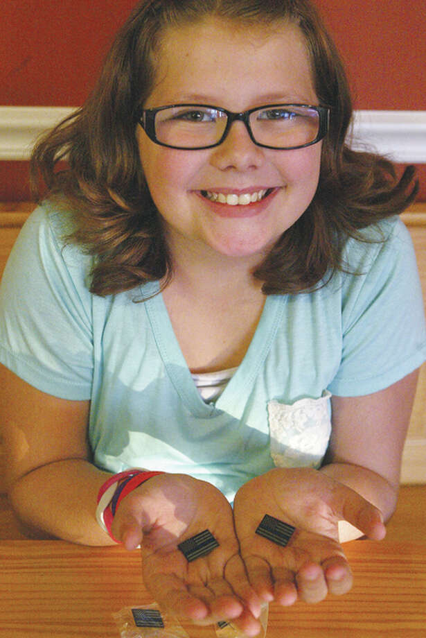 Brynlie Watson, 9, is selling pins to show support for police officers and to raise money for the Police Memorial Fund, which helps families of fallen police officers.