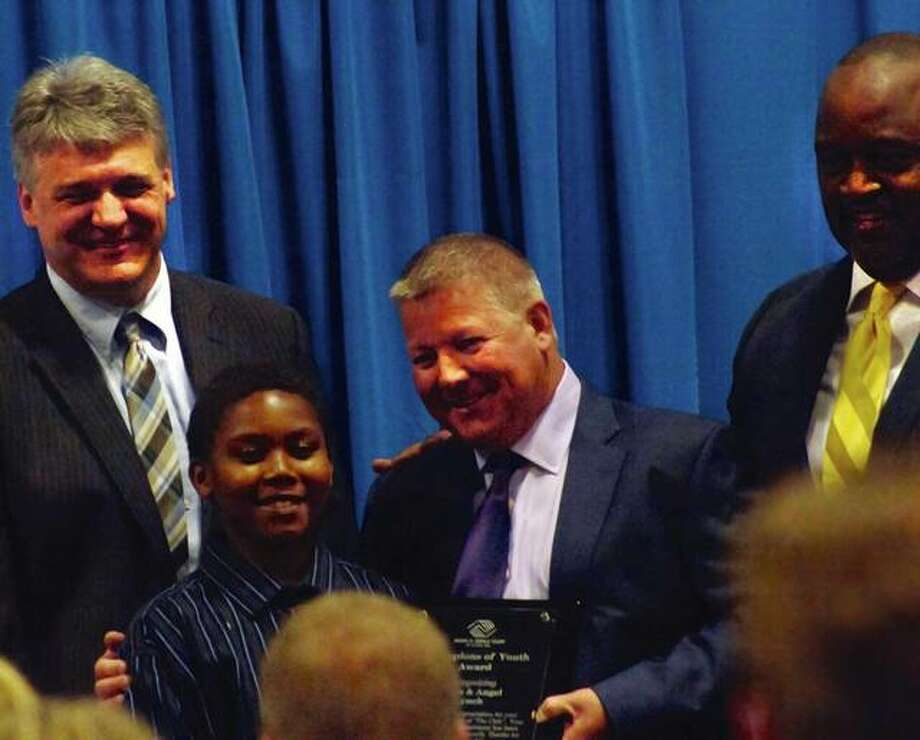 Miles Lynch, center, receives the Boys and Girls Club of Alton's Champions of Youth honor during the organization's annual fundraising awards dinner Thursday night at Lewis and Clark Community College Commons. He fit the role by bringing 8-year-old Tre'Shaun Holliday, a club member assisting at the event, to the stage to help him accept the award. Pictured far left is board President Bret Mayberry. Pictured to the far right is the club's Executive Director Al Womack Jr. Photo: NATHAN WOODSIDE | For The Telegraph