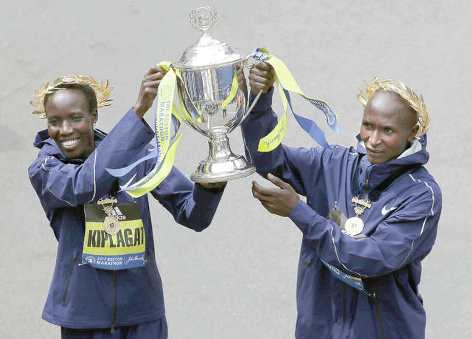 Edna Kiplagat, left and Geoffrey Kirui, both of Kenya, hold a trophy together after their victories in the 121st Boston Marathon Monday.
