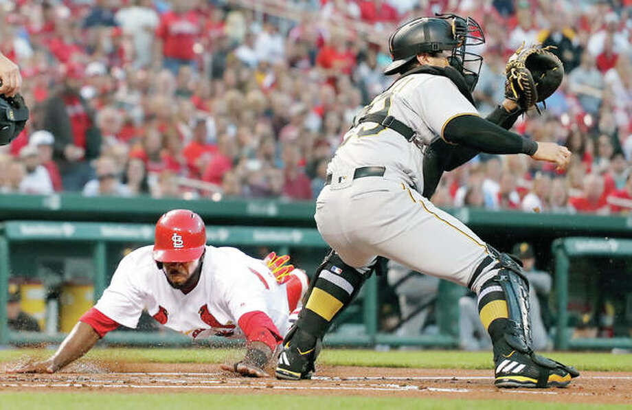 The Cardinals' Dexter Fowler, left, scores past Pirates catcher Francisco Cervelli in the first inning of Tuesday's game. Photo: AP