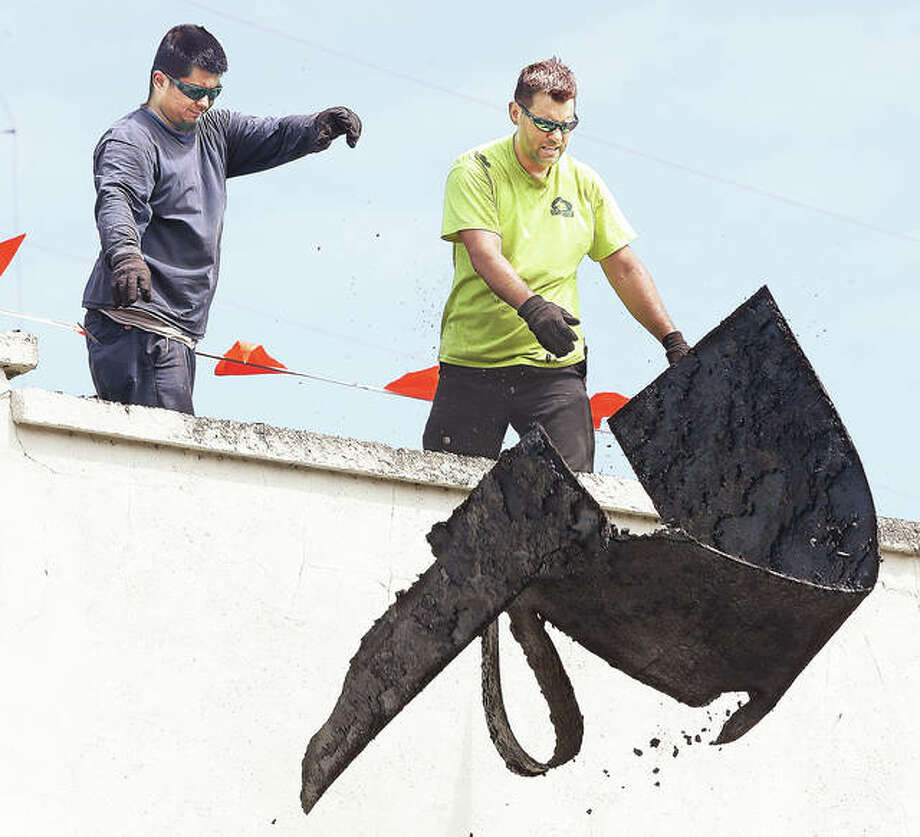 John Badman|The Telegraph Employees of Lakeside Roofing Inc. in Collinsville toss a piece of old roofing material off the downtown Hayner Public Library branch which is in the process of getting a new roof.