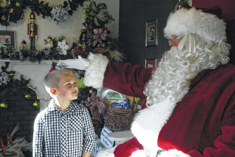 Henry Hinds, 5, visits with celebrity Santa Claus of the North Pole who had made a special trip down to his Jacksonville office Saturday in Central Park to hear what the nice boys and girls of Morgan County want for Christmas. In Hinds' case, it was a BB gun and an alarm clock to help wake him up for work in the morning. While Santa didn't comment as to who had made his annual naughty or nice list for 2015, he did hand out candy canes to all the boys and girls that came to see him. Photo: Nick Draper | Journal-Courier