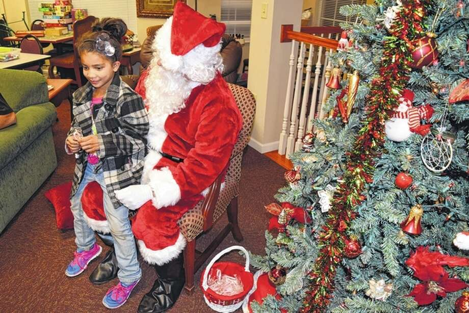 Jaycee Jackson, 7, sits on Santa Claus' lap Tuesday evening during the Cookies with Santa event at Knollwood Retirement Village in Jacksonville. Knollwood provided cookies and milk for children at the event. Jaycee is the daughter of Tiffany Duncan and stepdaughter of Lee Duncan of Jacksonville. Photo: Greg Olson | Journal-Courier