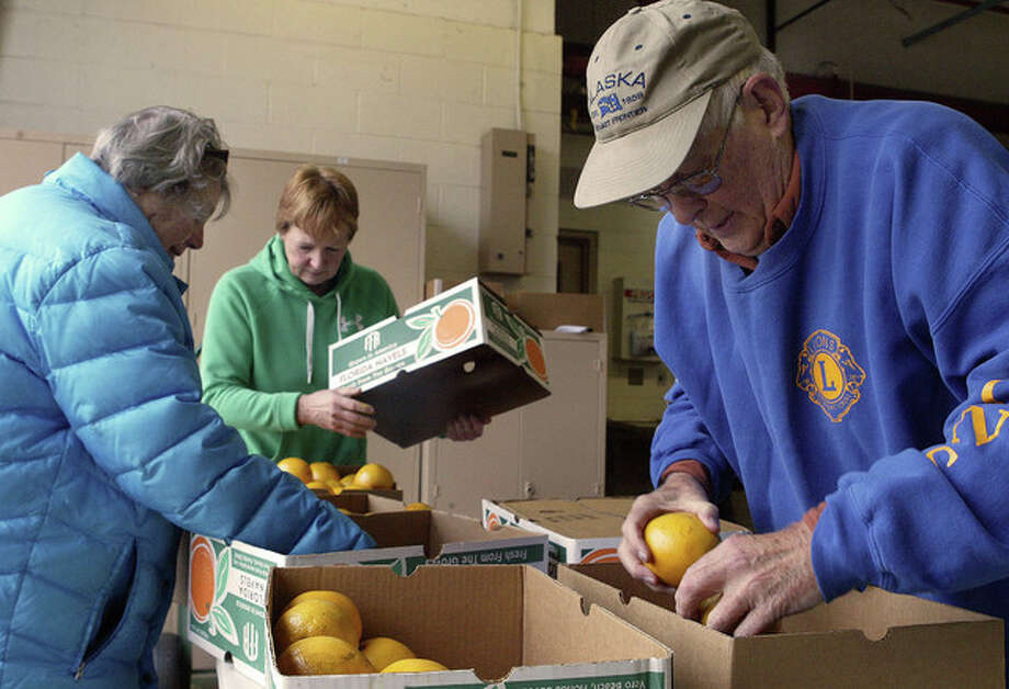 Barb Farrar (from left), Jane Truitt and Lions Club member Nick Farrar sort oranges Tuesday for the Lions Club's annual fruit sale. Those who have yet to place an order can buy fruit from 8 a.m. to 7 p.m. Thursday and 8 a.m. to 5 p.m. Friday at the garage in the rear of the Illinois School for the Visually Impaired at 658 E. State St. Photo: Nick Draper | Journal-Courier