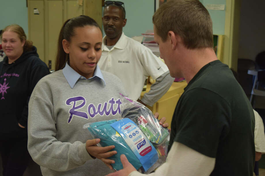 Miriam Wali-Uddin, 14, gives a bag full of assorted gifts to Joe Forrester at New Directions Heating and Cooling Center on Thursday. Photo: Nick Draper | Journal-Courier