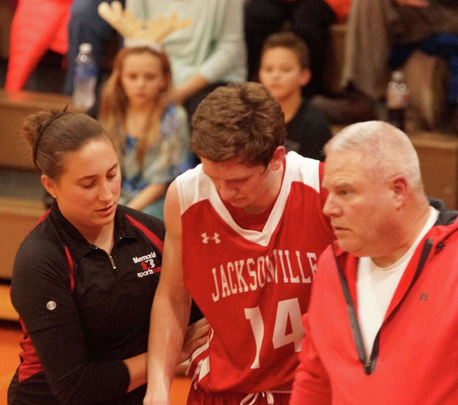 JHS senior Riley Dugan is helped off the floor by a trainer after being injured Friday night. Dugan left the gymnasium on crutches. Photo: Daniel L. Chamness | For The Journal-Courier