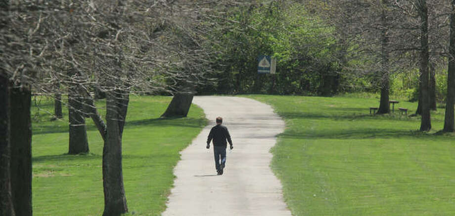 A hiker makes his way down the paved hiking trail at La Vista Park in Godfrey.