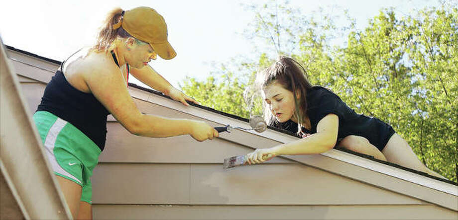 John Badman|The Telegraph Seniors from Marquette Catholic High School in Alton, like Abby Simonds, left, and Audrey Zigrang, were performing duties on Senior Service Day by painting near the roofline of a house in the 4100 block of Aberdeen Avenue in Alton. Marquette students were painting houses in both Alton and East Alton.