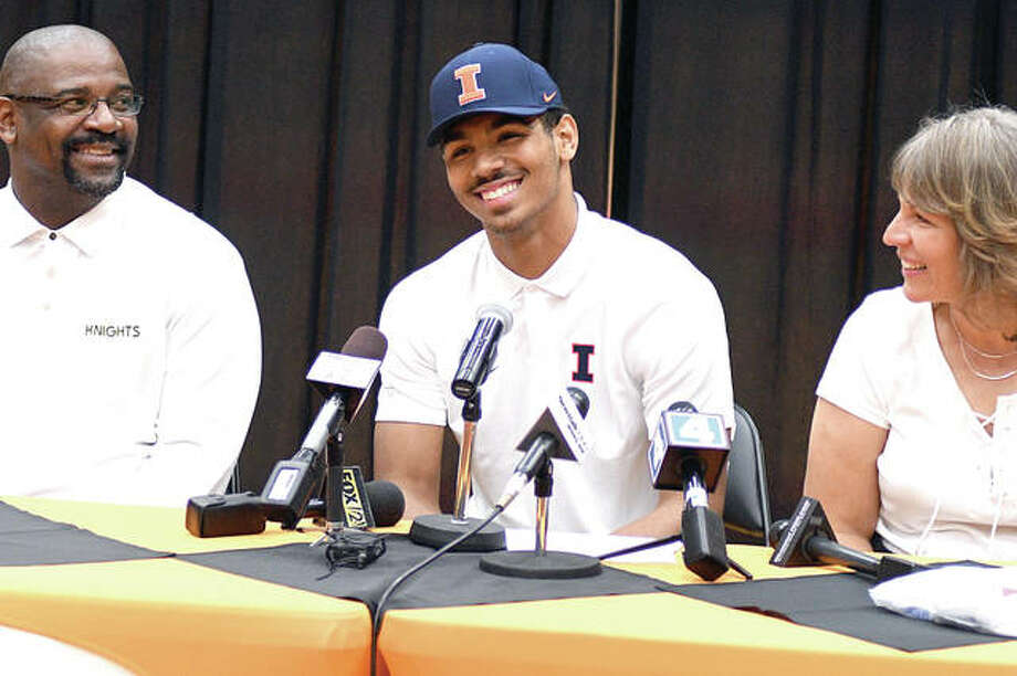 Mark Smith, center, smiles with his dad, Anthony, on one side and his mother, Yvonne, on the other after making his announcement Wednesday night that he will be playing basketball at the University of Illinois. Photo: Dan Cruz | For The Telegraph