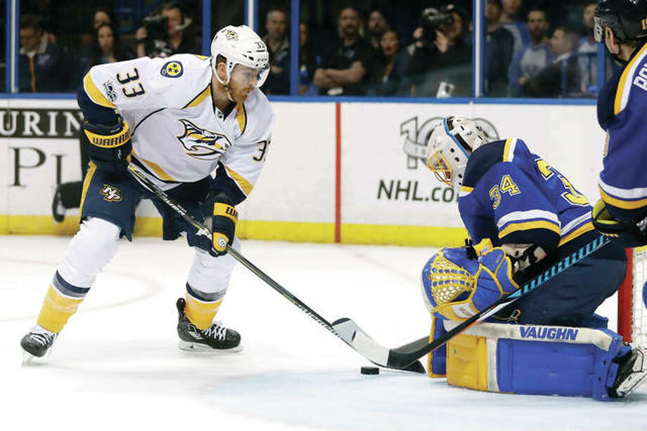 The Nashville Predators' Colin Wilson, left, reaches for the puck as Blues goalie Jake Allen defends during Wednesday night's game in St. Louis. Photo: AP