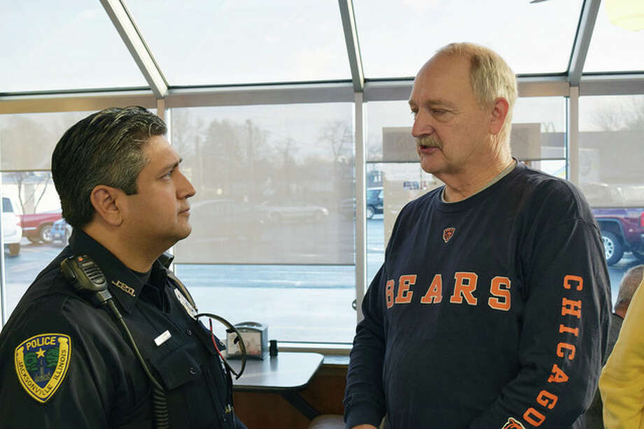Jacksonville Police Patrolman Tino Vasquez (left) speaks Wednesday with retired Illinois State Police Trooper Jim Paul of Jacksonville during a pre-Christmas Coffee with a Cop session at Hardee's on West Morton Avenue. Coffee with a Cop is designed to introduce police officers to the public and give people the chance to voice concerns and ask questions. Paul said he and other retired state troopers get together once a month. Photo: Greg Olson | Journal-Courier