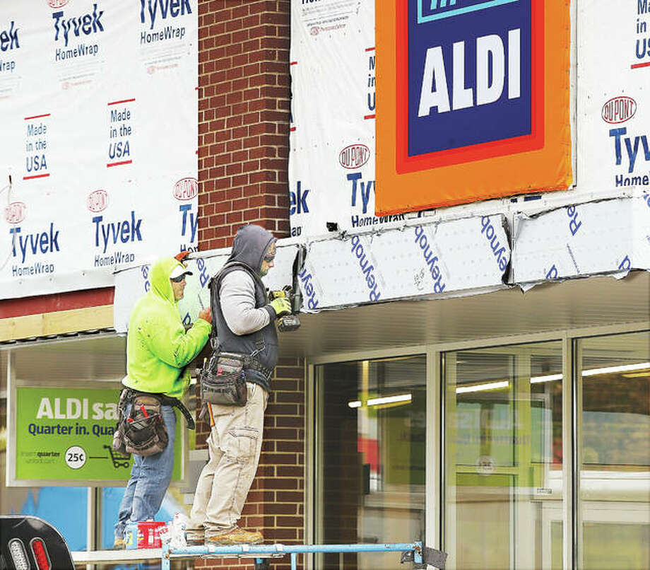 Two workers put the finishing touches on the exterior of the Aldi food store expansion Thursday on the Homer Adams Parkway at Seminary Street. The store, which has undergone an expansion and renovation, will re-open to customers on Monday, May 1 and hold a grand re-opening on Friday, May 5. Photo: John Badman | The Telegraph