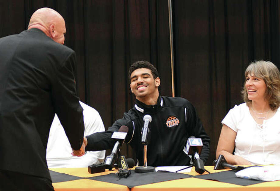 Edwardsville Tigers basketball coach Mike Waldo (left) shakes hands with Mark Smith after Waldo's brief comments during a ceremony revealing Smith's signing with Illinois on Wednesday night at Lucco-Jackson Gym in Edwardsville. Mark's mom Yvonne Smith is seated at right.