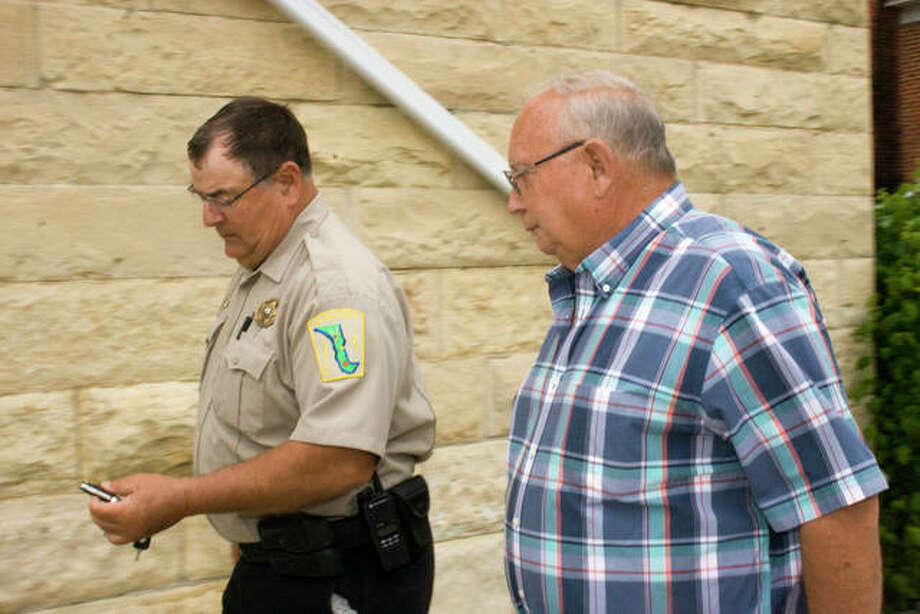Michael Dean, 59, of Kampsville, is led away from the old Calhoun County Courthouse by Sheriff Bill Heffington. Dean pleaded guilty Thursday to assault and drug possession charges from a 2011 incident, and will serve 1.5 years in prison. Photo: Alex Heeb | The Telegraph