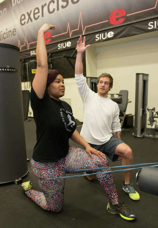 SIUE senior Cody Snyder, a native of Shelbyville, leads a participant in stretches during one of this project team's training sessions. Photo: For The Telegraph
