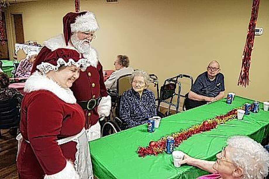 Mr. and Mrs. Claus visit with the seniors Friday at Heritage Health Therapy and Senior Care. The group enjoyed cookies, drinks, Christmas tunes and card games. Staff got festive with an ugly sweater contest and family came to visit their loved ones while getting a pic with old Saint Nick. Photo: Nick Draper   Journal-Courier