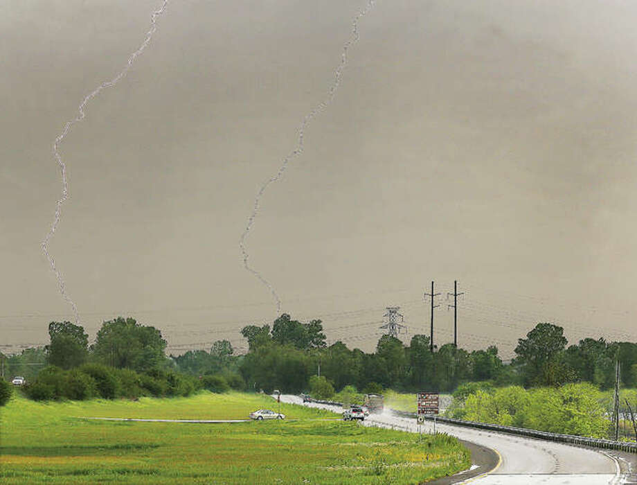 Lightning strikes in two places Friday near the lower lanes of U.S. Route 67 in West Alton, Missouri. The National Weather Service web site is predicting the river to rise 10 feet over the weekend to a level of 27 feet in Alton, nearing the moderate flooding level. That level of water will close Missouri Route 94 and the access road to the Lincoln Shields Recreation Area, both in West Alton.