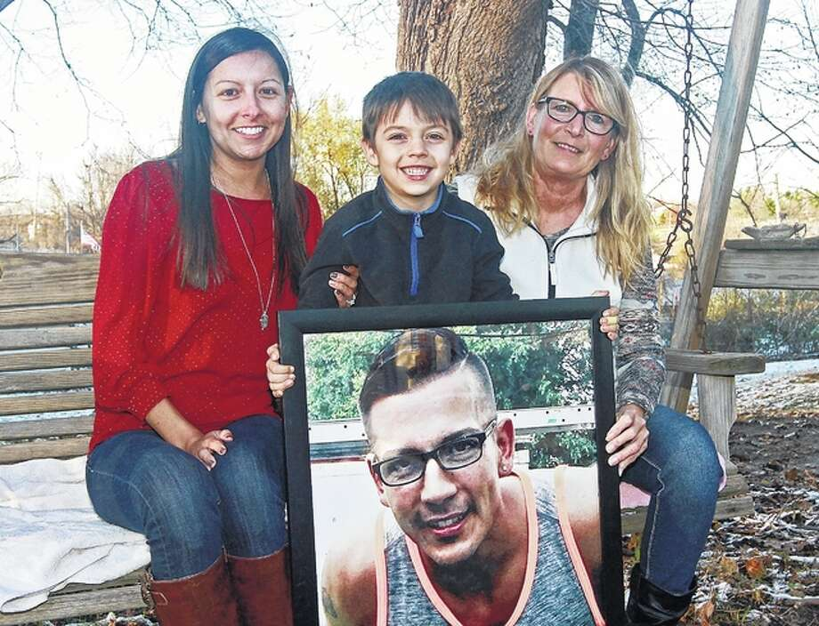 Jayden Martinez (center) poses with a photo of his father, Joseph Martinez, along with Joseph's mother, Anita Martinez (right) and sister, Breanna Flynn, in Barry. Joseph Martinez died July 12 of a heroin overdose. Photo: Michael Kipley | The Quincy Herald-Whig | AP