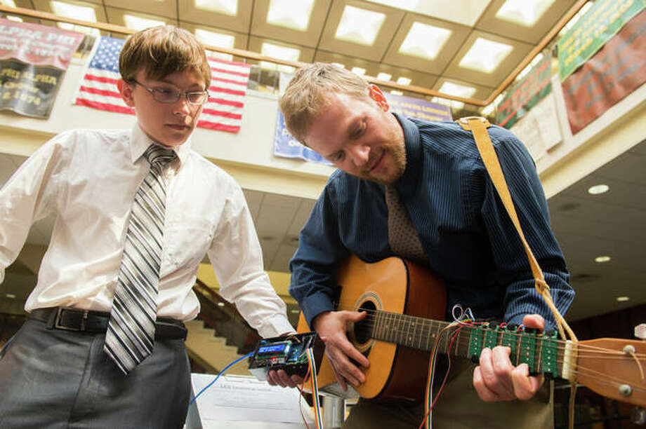 Nicholas Carter, of St. Charles, Missouri, and Dan Ashbaugh, of Altamont, demonstrate the usability of their team's LED Learning Guitar.