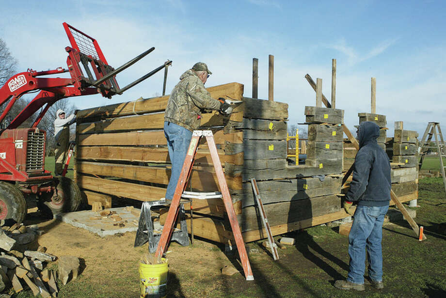Prairie Land Heritage Museum volunteers Wilbert Delong (from left), Dale Lair and Virgil Huseman work on rebuilding the 1827 Haskell Cabin, which was donated by the Tom and June Brackett family. The cabin stood south of Exeter until it was dismantled in November. Photo: Greg Olson | Journal-Courier