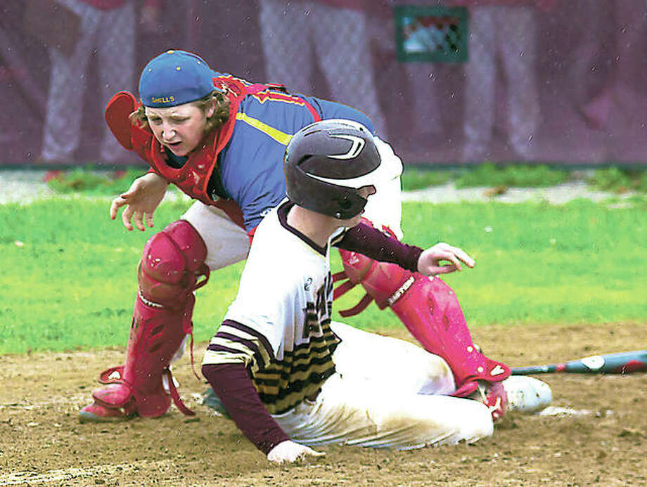East Alton-Wood River's Christian Hunter slides safely under the glove of Roxana catcher Chad Mott on a sacrifice fly off the bat of Gage Booten Monday. The Shells held on for a 4-3 victory. Photo: Nathan Woodside | For The Telegraph