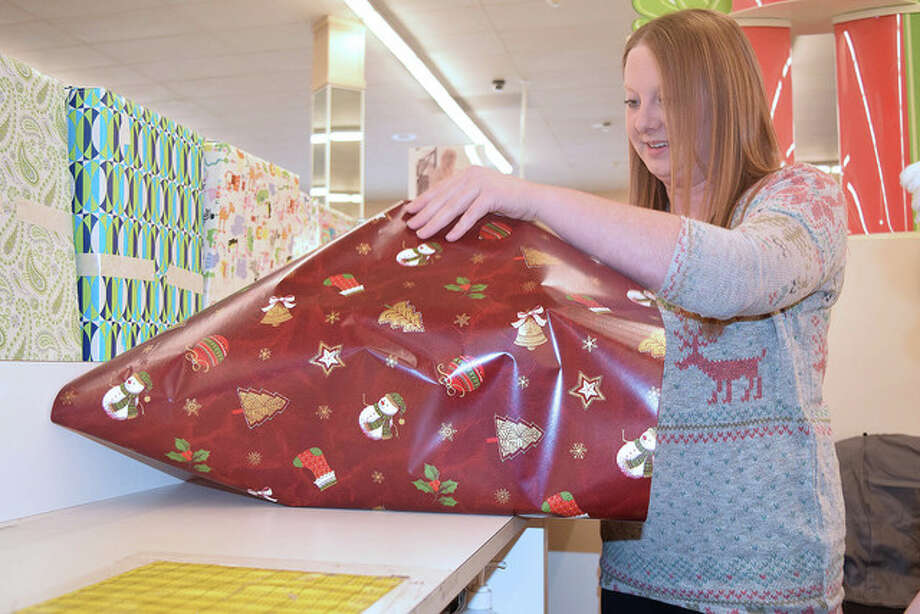 Sierra Hunt of Franklin, an employee at Goody's in Lincoln Square Shopping Center, wraps a last-minute present Thursday. The last shopping day before Christmas ensured that business was bustling throughout the day. Photo: Nick Draper | Journal-Courier