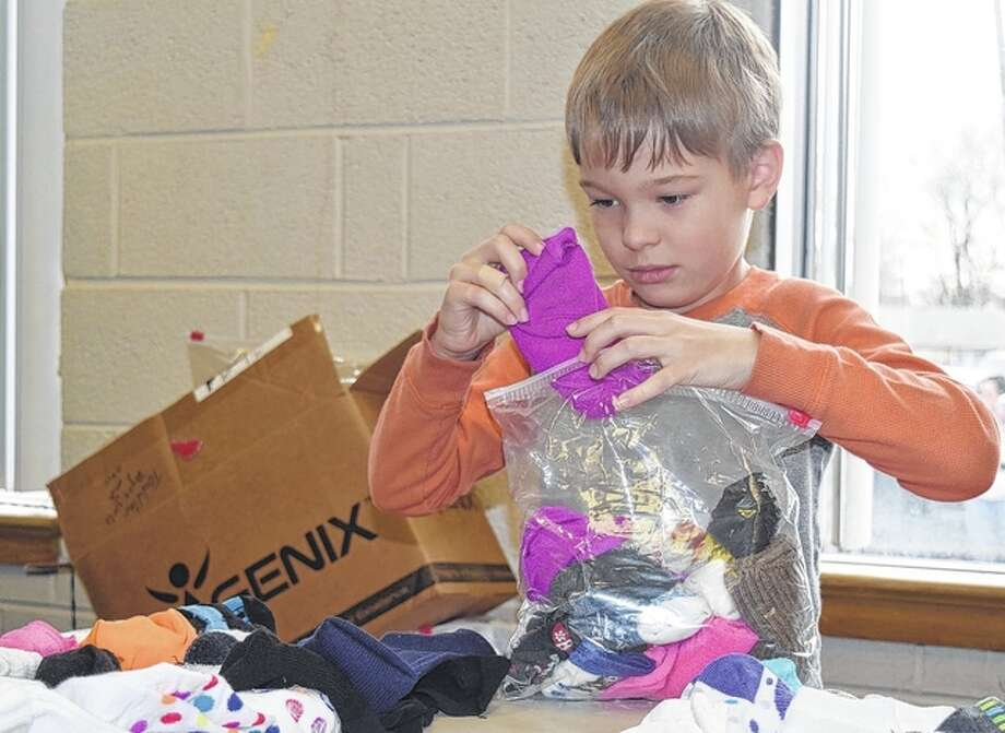 Kellon Oldenettel sorts through socks during The Salvation Army's weekly commodities distribution this week. Photo: Nick Draper | Journal-Courier