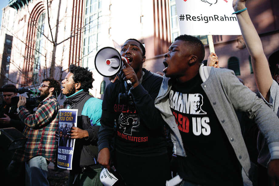 "Jose M. Osorio | Chicago Tribune (TNS) Protesters yell ""16 shots and a cover up"" as they stop traffic in Chicago's Loop after details of the shooting of a teenager came to light."