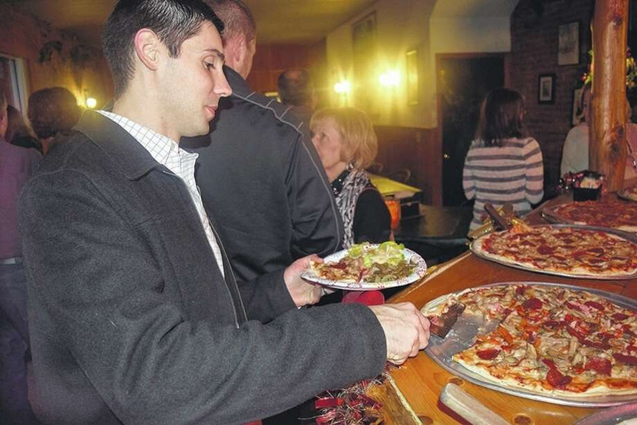 Kiwanis member Brad Probst grabs a slice of pizza Tuesday at a year's-end Kiwanis gathering at Leo's Pizza. Because of an influx of new members this year, the Jacksonville group decided to have the party to give everyone a chance to mingle. Each member received a nut or a bolt and, as they socialized, they tried to find their match. Photo: Nick Draper | Journal-Courier