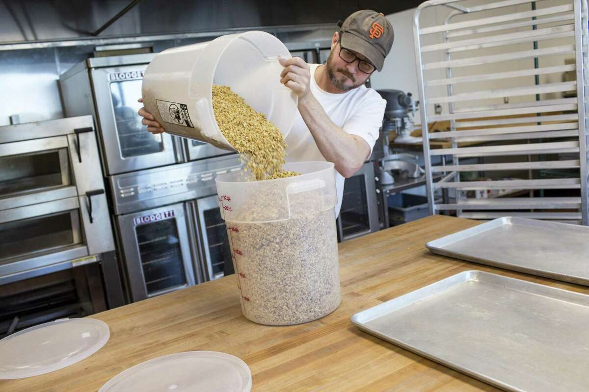 Garrett Lamb, owner of Garrett's Granola, combines granola buckets at Eclectic Cookery in Hunters Point.