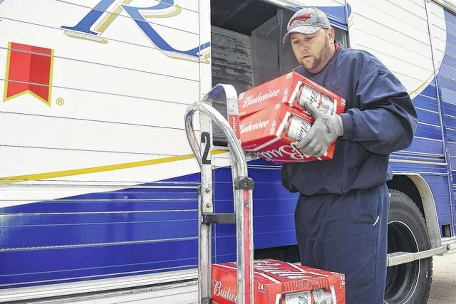 A. Gaudio & Sons driver Phil Pratt unloads cases of beer at Fast Stop on South Main Street in South Jacksonville. The beverage distributor is the key sponsor of the Alert Cab program, which provides free rides home from Jacksonville bars and restaurants for those who have had too much to drink during holiday celebrations. Photo: Nick Draper | Journal-Courier