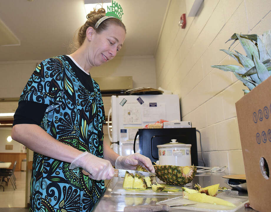Kori Daniels, hostess for the Jacksonville Area Senior Center, slices pineapple Thursday in preparation for the center's New Year's party. Seniors were being treated to different foods and snacks at the afternoon bash.