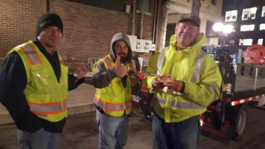 City workers eating pizza from Karen Brueggeman, the manager of 300 State Street Bar and Grill. Photo: For The Telegraph