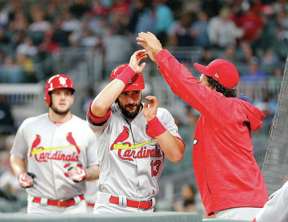 The Cardinals' Matt Carpenter (13) is greeted at the dugout after hitting a two-run home run in the third inning Saturday night in Atlanta.