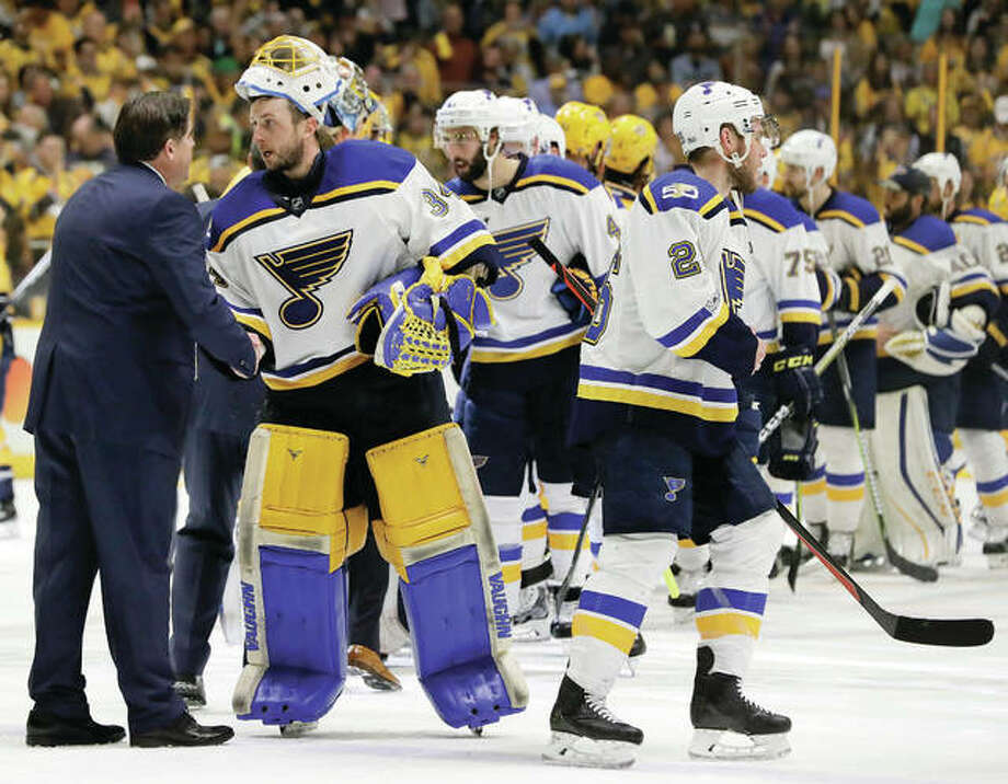 Blues goalie Jake Allen shakes hands with Nashville Predators coach Peter Laviolette (left) after the Predators defeated the Blues in Game 6 of a second-round NHL playoff series Sunday in Nashville, Tenn. The Predators won 3-1 to win the series 4-2. Photo: Associated Press