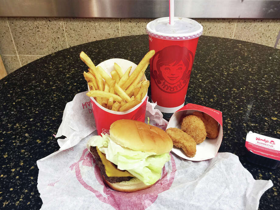 "A ""4 for $4 deal"" is seen at a Wendy's restaurant in New York. Another price fight is breaking out among the country's biggest burger chains, this time with meal combos designed to make people forget about the once ubiquitous dollar menus. Photo: Candice Choi 