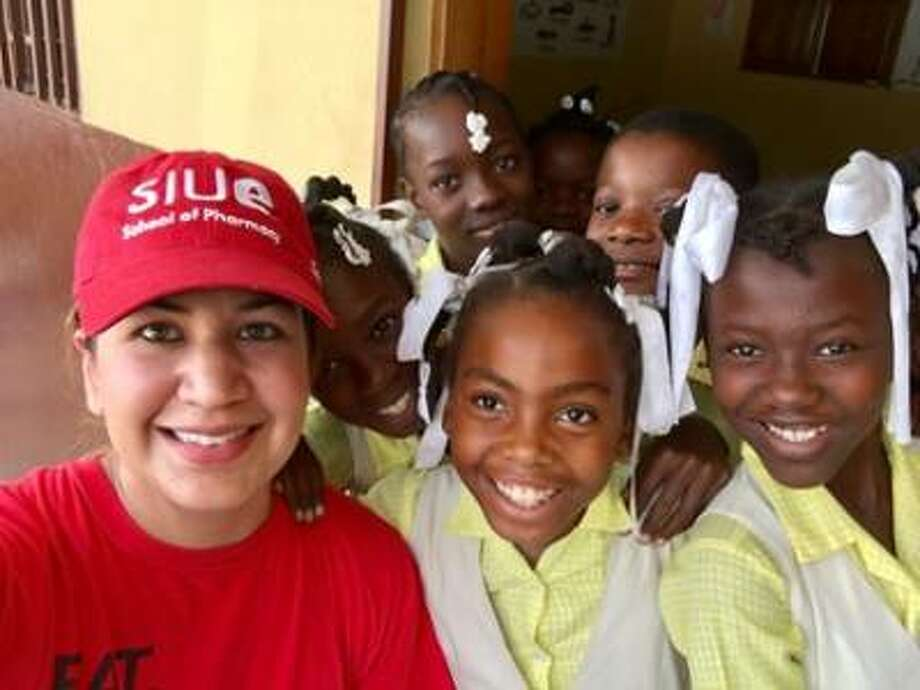Misty Gonzalez, PharmD, clinical associate professor in the SIUE School of Pharmacy smiles with a group of girls from Haiti while participating in a medical mission trip. Photo: For The Telegraph