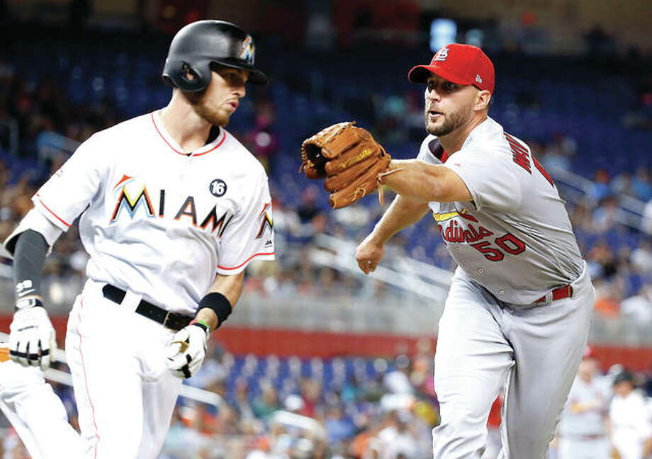 Miami's JT Riddle, left, is tagged out by Cardinals pitcher Adam Wainwright as he heads for first base in the fifth inning Tuesday night in Miami. Photo: AP