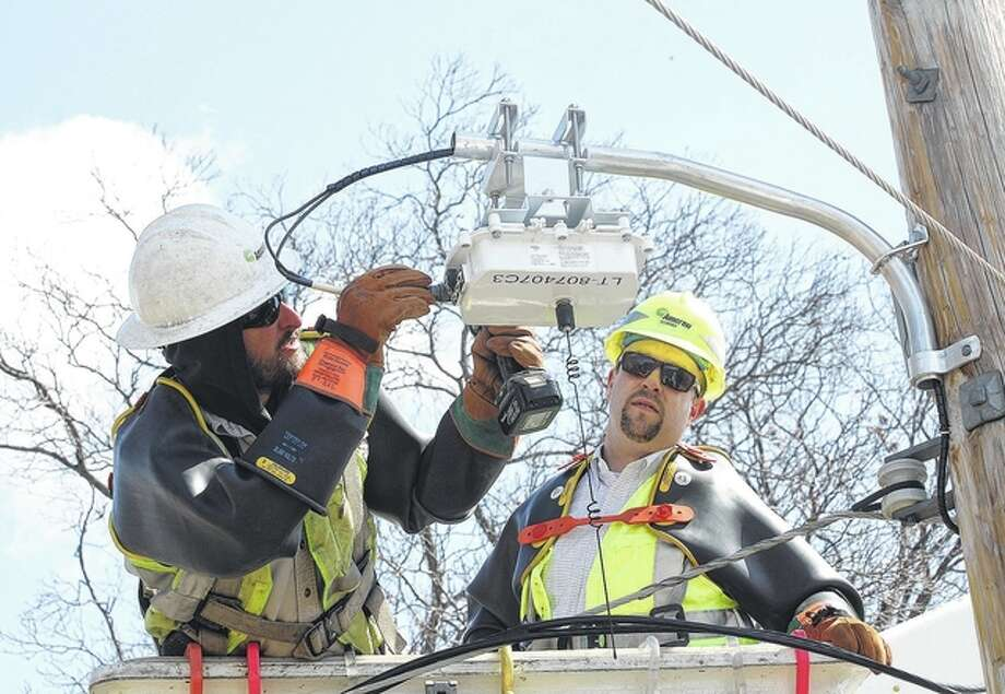Photo courtesy of Ameren Illinois Drew Edwards (left), a journeyman lineman for Ameren Illinois, installs advanced technology on a power pole as communications supervisor Jon Shockley oversees the installation.
