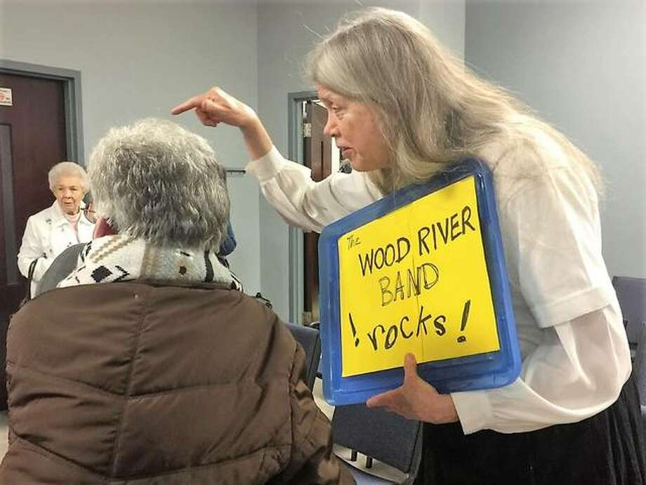 Wood River Municipal Band member Linda Brubaker speaks to an attendee of the Wood River City Council meeting May 1 while displaying a sign showing her support of the band. The 100-year-old program is in danger as it faces funding cuts from the city. Photo: Brittany Johnson | The Telegraph