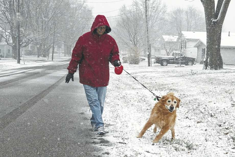 Mary Jane Esslinger walks her 12-year-old retriever, Tyler, in South Jacksonville on Saturday as snow falls. A winter storm provided the first real taste of winter this season to west-central Illinois. Photo: Nick Draper | Journal-Courier
