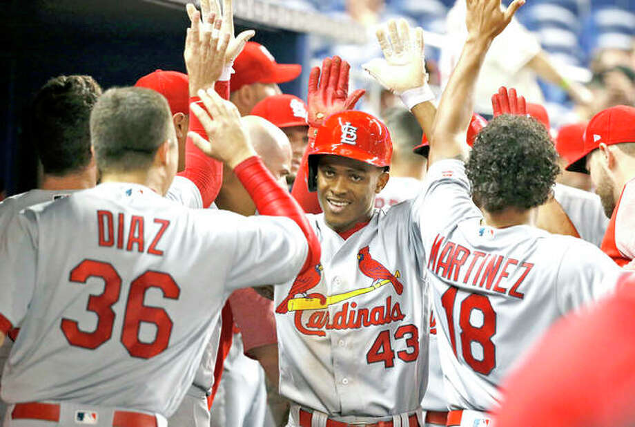 The Cardinals' Magneuris Sierra (43) is congratulated by teammates after scoring on a triple by Dexter Fowler in the sixth inning Wednesday night in Miami. Photo: AP
